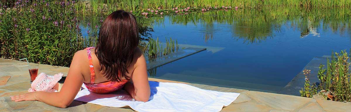 Frau liegt am Schwimmteich